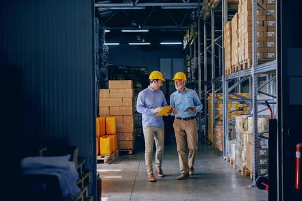 Two men talking inside a warehouse
