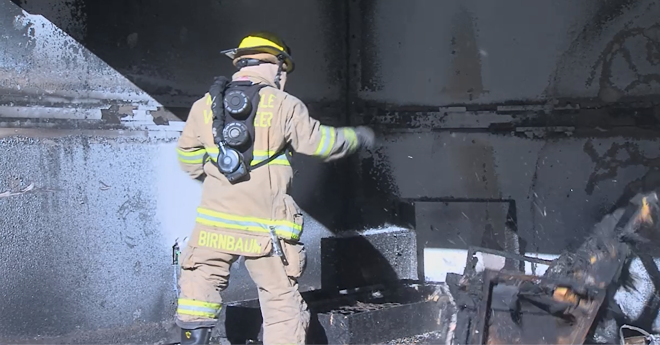 Firefighter in full gear wearing the respiration protection device in a burnt room.