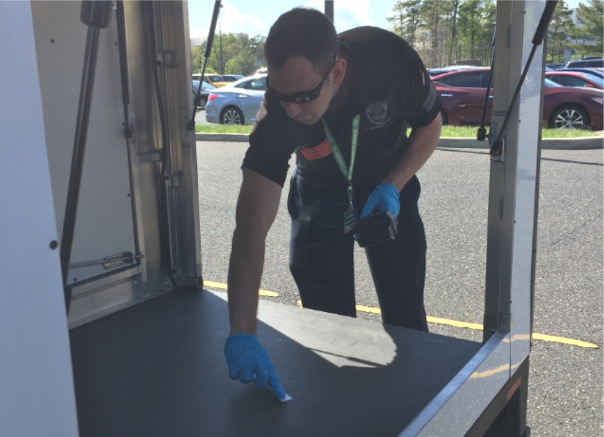 A law enforcement officer uses a handheld ETD to collect samples during the vehicle screening scenario.