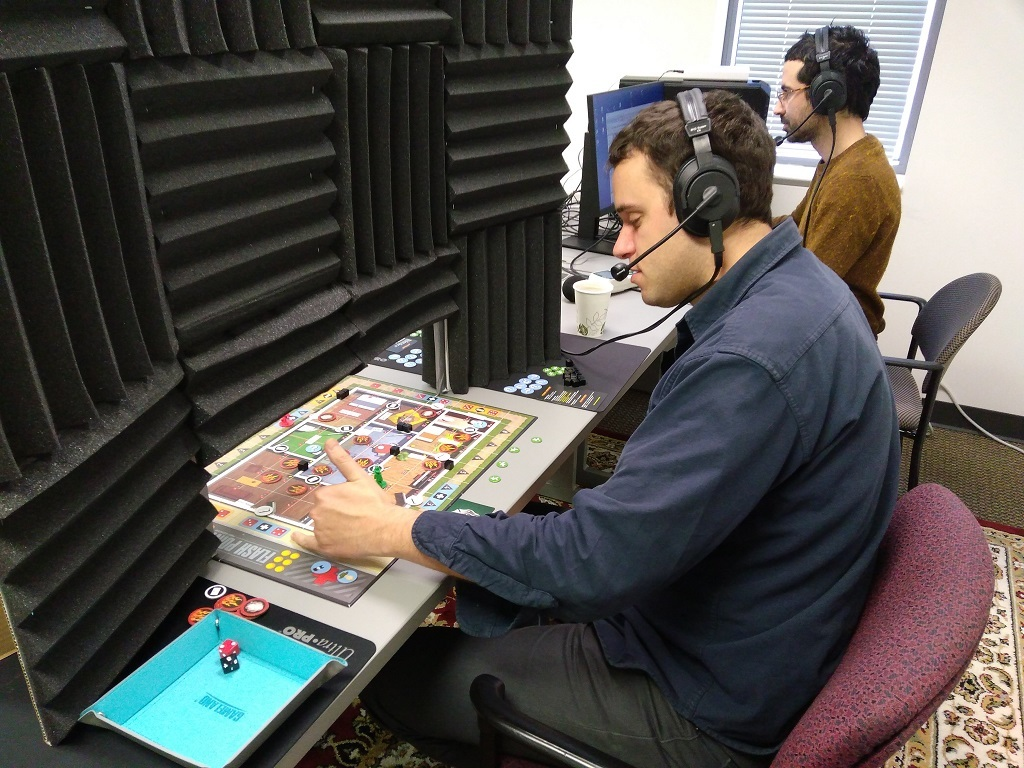 An audio engineer (wearing red pants) at the Linguistic Data Consortium at UPENN collects data from study participants who are playing board games.