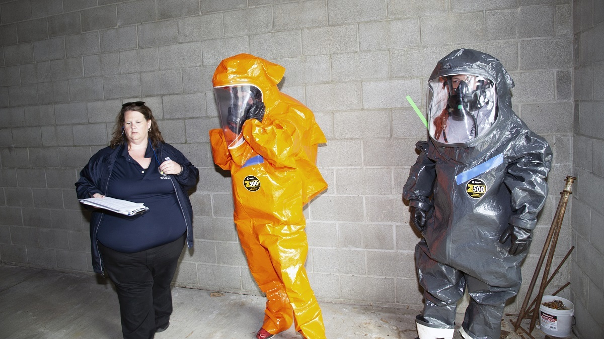 An evaluator looks on and captures feedback, a pair of first responders, wearing personal protective equipment and in-suit communications gear.