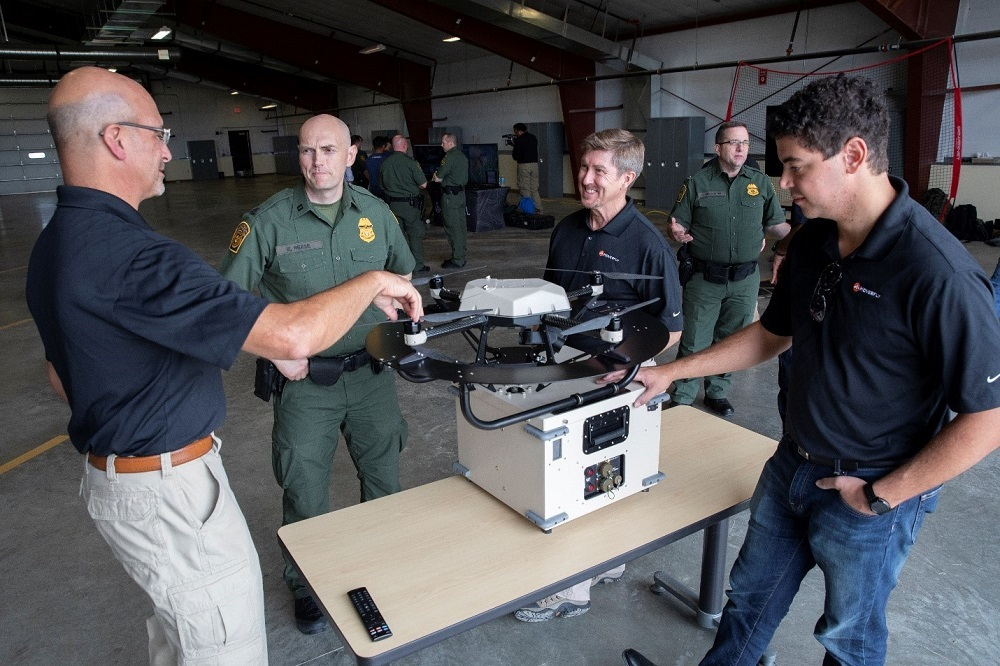 A technology provider discusses capabilities of their tethered Unmanned Aerial System with a USBP agent.