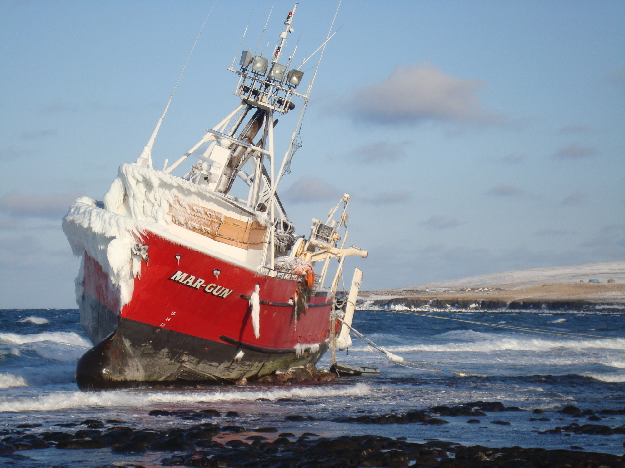The fishing vessel Mar-Gun sits grounded with heavy ice accumulation on the north end of St. George Island in Alaska, April 11, 2009. A vessel's center of gravity can rapidly rise when freezing spray accumulates high above the main deck. U.S. Coast Guard photo.