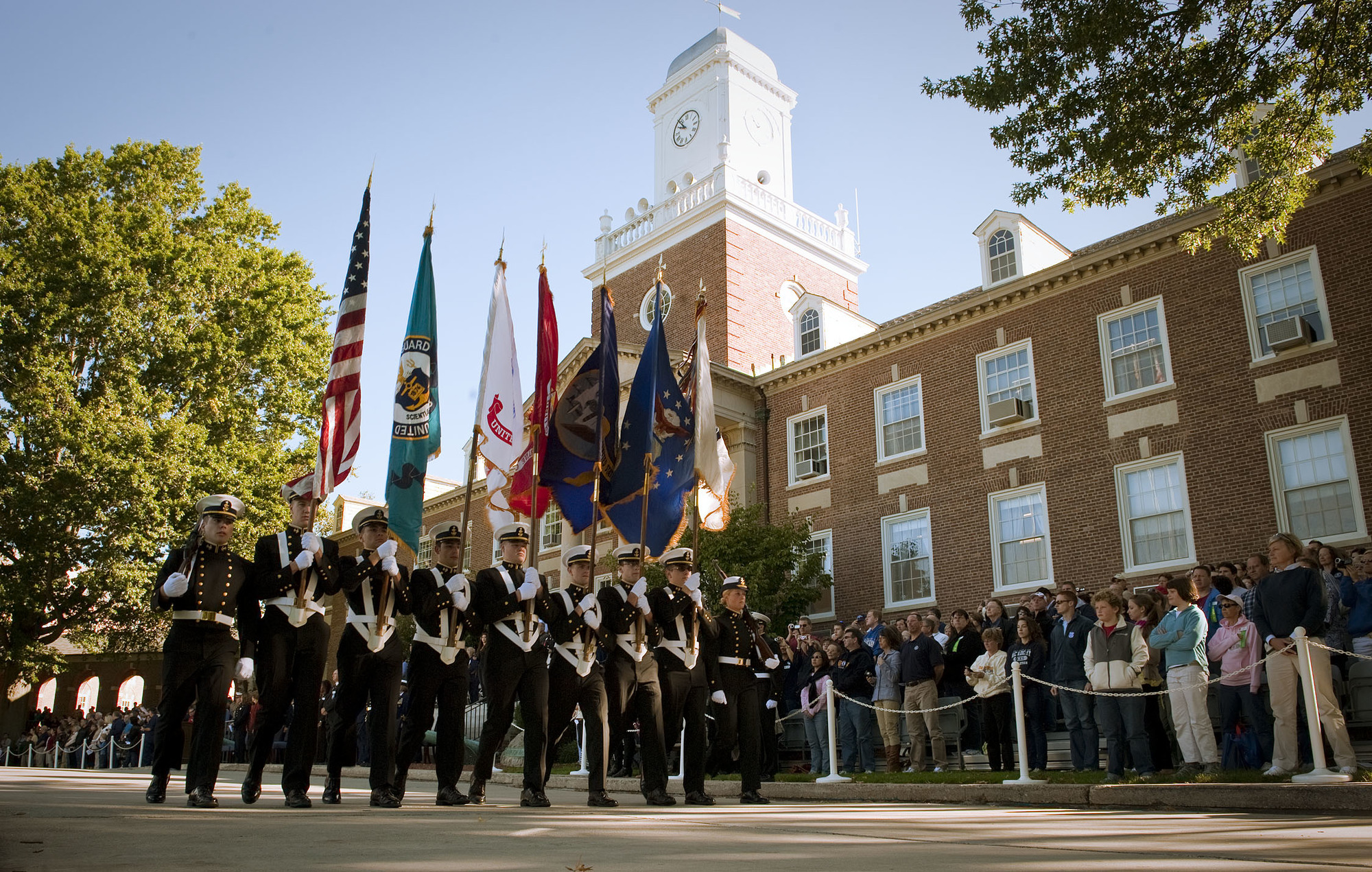 A color guard passes in front of Hamilton Hall at the Coast Guard Academy in New London, Conn.