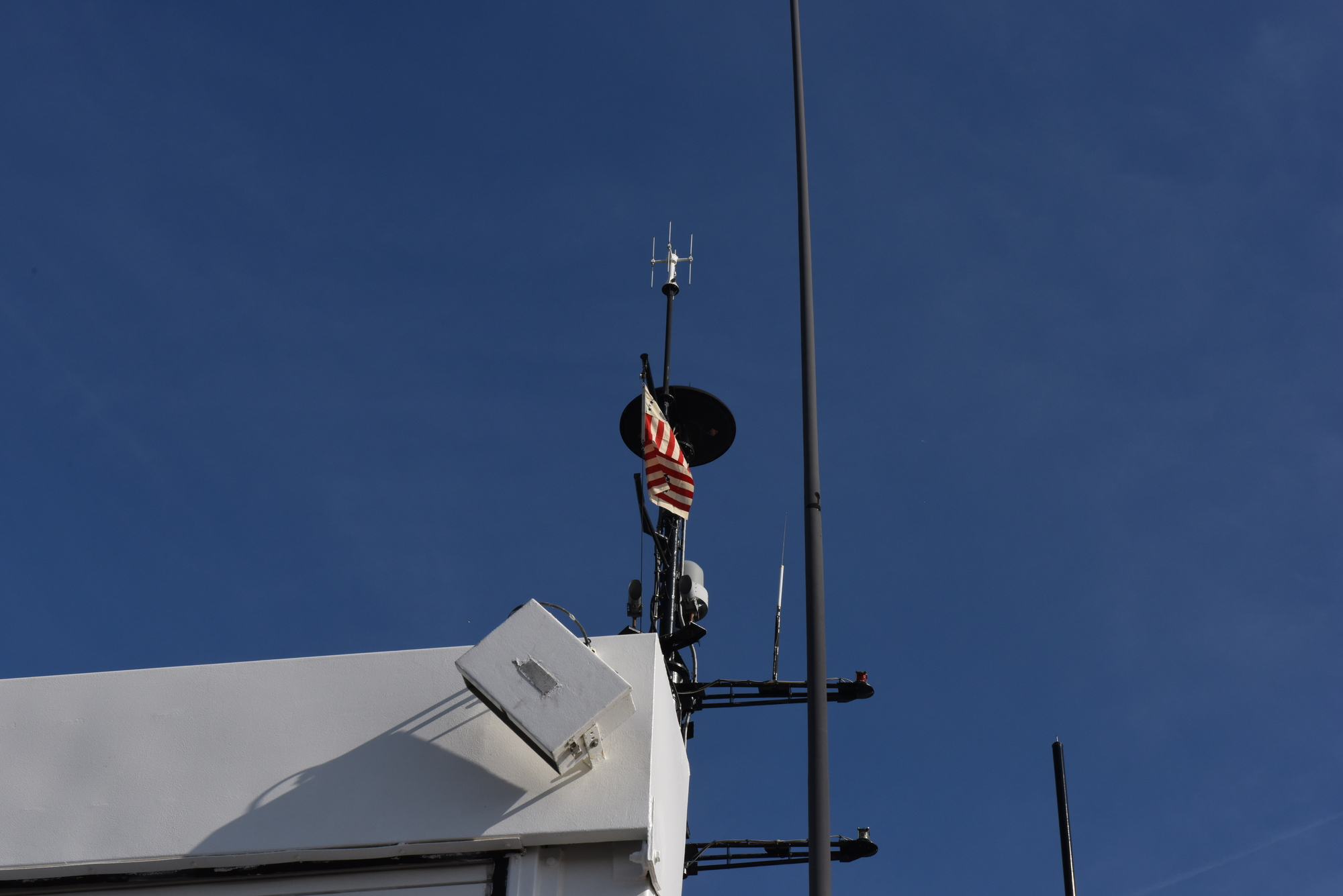 Historical Coast Guard ensign from WWII flies above new cutter with same namesake.