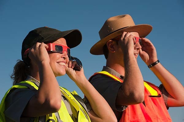 people watching a solar eclipse with glasses