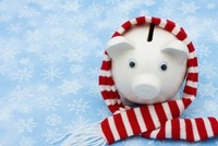 Piggy bank wrapped in a scarf against a snowy background