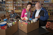 A group of people shopping in a food pantry.