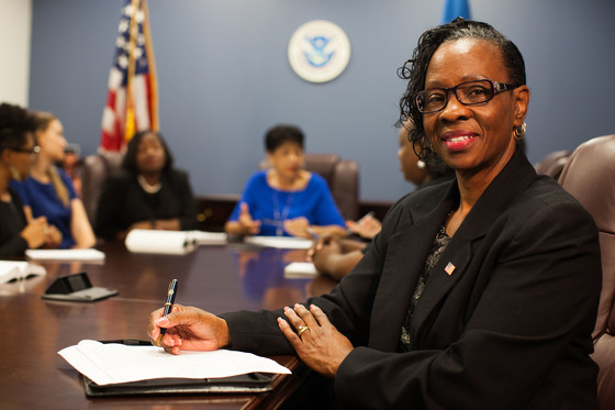 A Black woman siting at a desk and smiling at the camera while holding a pen above a pad of paper. Various women in the background at the same desk in front of the DHS Seal and American flag engage in conversation.