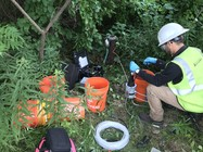 A worker samples groundwater using low-flow sampling protocols.