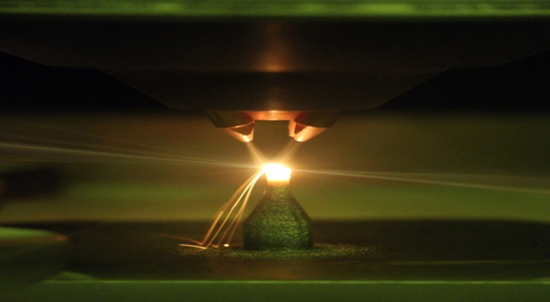 Photo of three nozzles spraying onto a 3D printed material