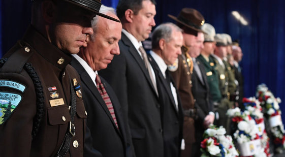 A line of uniformed law enforcement officers standing in front of wreaths.