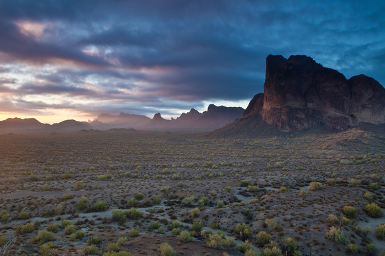 The Eagle Tail Mountains rise over a flat desert as the sky darkens in the distance.