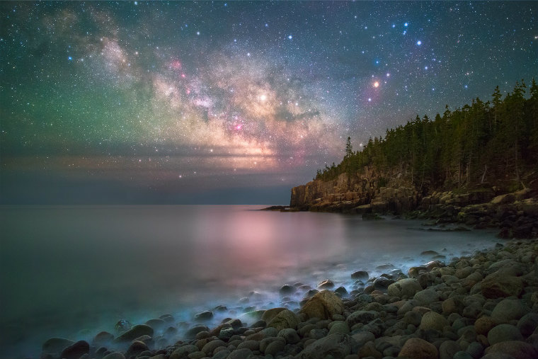 Bright clusters of stars glow in the night sky above the ocean and a rugged coastline covered in rocks and trees.