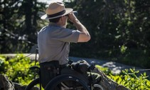 Glacier National Park Ranger in wheelchair looking through binoculars