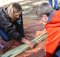 mother and son tying sticks together