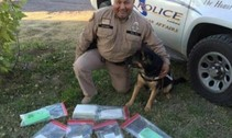 BIA Officer and Dog kneel by drugs from drug bust