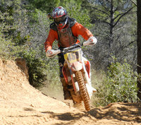 OHV dirt bike rider zooms through a dusty trail wearing protective gear and helmet