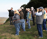 Participants stand outside in fall clothing peering out over cliff edge