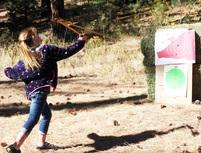 young girl throws atlatl at target