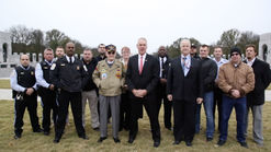 Secretary Ryan Zinke stands with veterans in front of wwII Memorial in Washington DC on overcast day