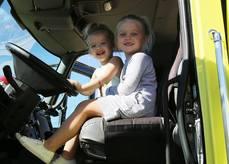 Daughters enjoy a firetruck drivers seat