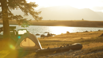 Tent and Canoe by lake.