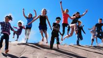Kids jumping on sand dune