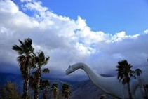 A large plastic dinosaur by palm trees
