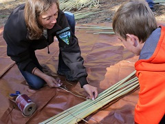 BLM Archaeologist Jennifer Rovanpera shows an Archaeology Day participant the beginning steps of creating a mat from tule reeds.