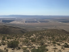 A photo of a solar array at the bottom of a desert valley.
