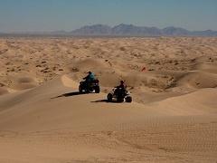 Two OHVs crawl across desert dunes