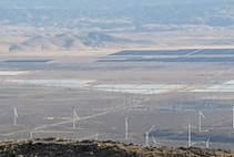 A desert valley with solar panels and wind turbines.