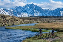 Two bikers by a stream, with snow cap mountains in the background.
