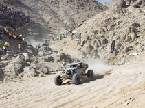 Off road vehicle racing in a desert canyon.