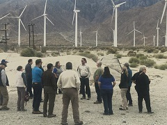 A photo of a group of people meeting in  the desert with windmills visible in the background.