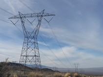 High voltage power line and tower on a desert hill.