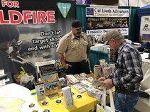 BLM employee speaking to a visitor at a booth.