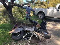 A BLM employee standing over a pile of trash.
