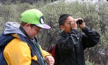 Two boys stand together outside while one of them looks through binoculars.