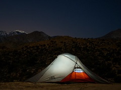A tent lit up in the night.