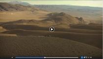 A video still of horses running through hills.