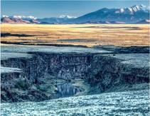 A dark canyon in a beautiful landscape.