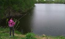 An angler fishing by a lake.