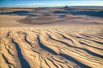 Sand desert with sharp peak in the distance.