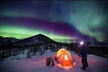 Aurora Borealis in the sky over a camper and a tent.