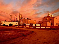 A photo of a factory during sunset.