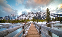 A boardwalk over water with mountains in the background.
