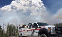 A fire truck with a bellowing smoke column.