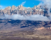 Desert mountain with low clouds and snow.